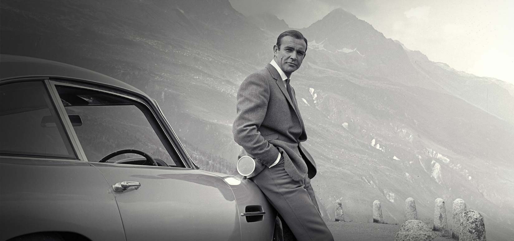 A silver aston martin db5 in goldfinger: sean connery in a custom fitted grey suit