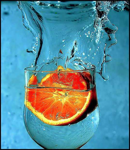 dropping orange in glas of water