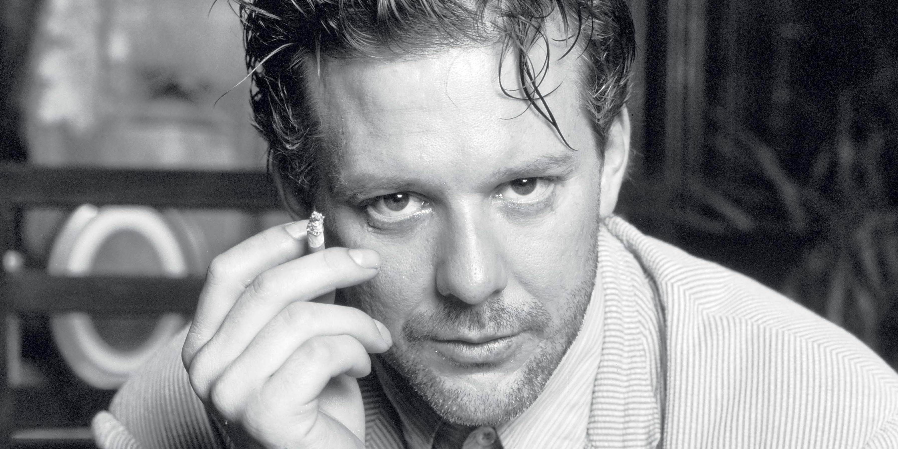 Mickey Rourke, star of Angel Heart,  wearing a striped shirt and jacket and smoking a cigarette