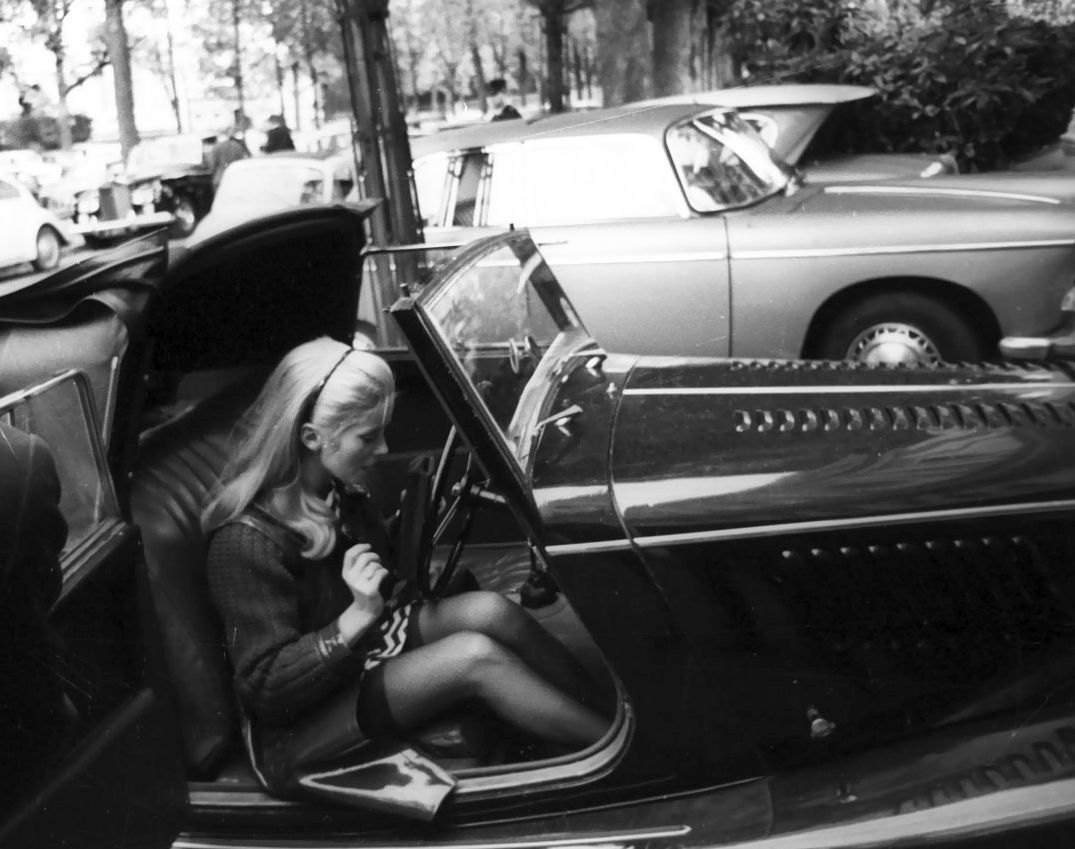 Catherine Deneuve driving a Morgan roadster in Paris