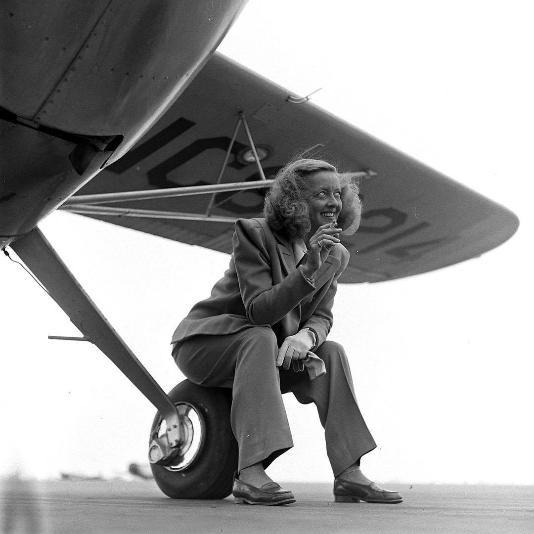Bette Davis seated on a wheel beneath the wing of an airplan